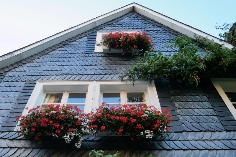 Window boxes of flowers hanging on slate walls.