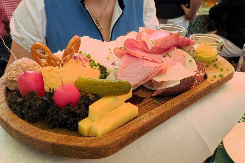 platter of cheese, ham, radishes, pickles on a wooden platter